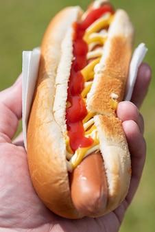 手は上からの外出先でジューシーなホットホットドッグファーストフード食品を保持します