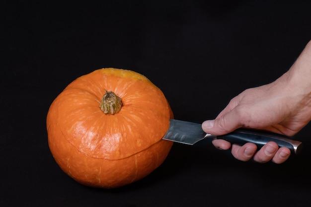 손은 칼을 들고 검은 배경, 클로즈업, 복사 공간에 격리된 둥근 주황색 호박을 자릅니다. 잭 랜턴 준비를 위한 단계별 지침. 1 단계