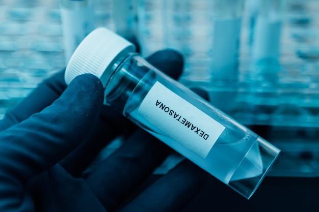 手はデキサメタゾンが入った実験用チューブを持ち、covid-19コロナウイルス治療