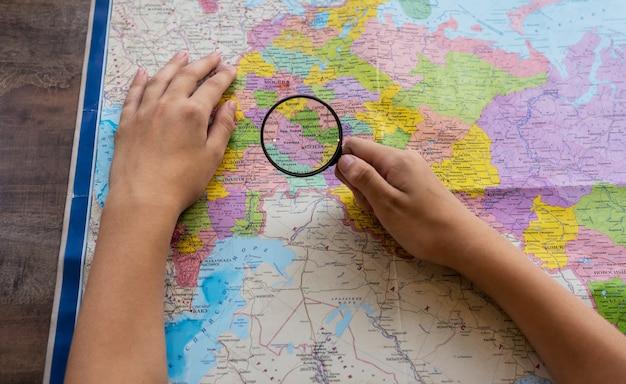손에는 돋보기가 있습니다. 세계지도 위. 여행 개념입니다.