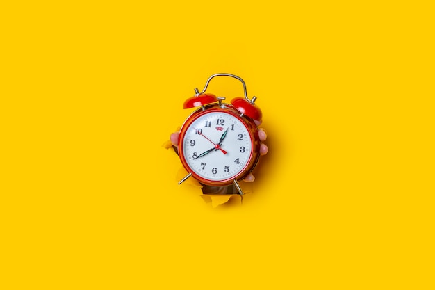 Рука держит красные часы в отверстии на рваном желтом фоне.