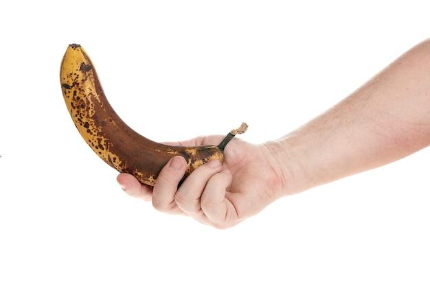 손은 디자이너를 위한 흰색 배경 템플릿에 익은 바나나를 들고 있습니다.