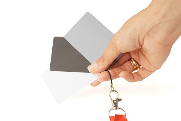 手は、白い背景のホワイトバランスを調整するための灰色のカードのセットを保持し、