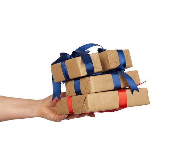 Рука держит стопку обернутых подарков в коричневой крафт-бумаге с завязанными шелковыми бантиками