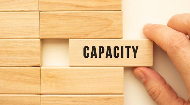 手は、capacityというテキストの付いた木製の立方体を持っています。ポジティブシンキングのコンセプト