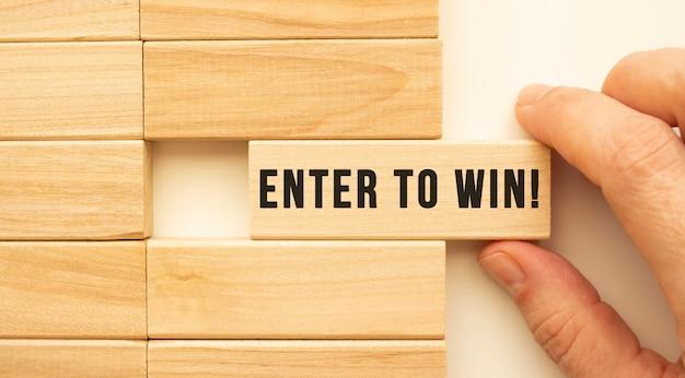 手には、enter towinというテキストが付いた木製の立方体があります。ポジティブシンキングのコンセプト
