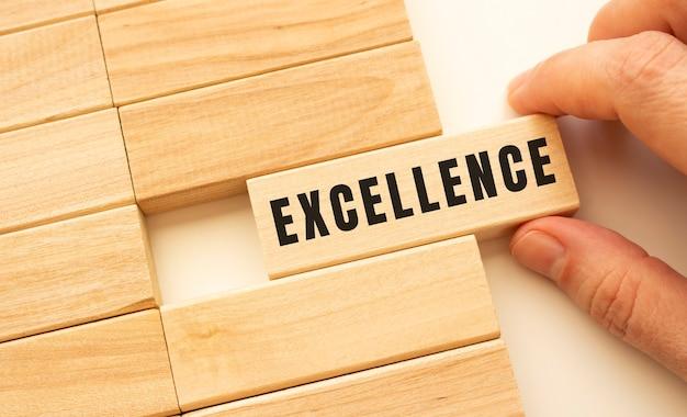 Рука держит деревянный куб с надписью excellence