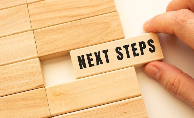 Рука держит деревянный куб с текстом следующие шаги. концепция позитивного мышления