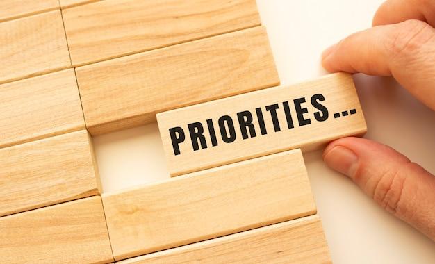 손에는 priorities 텍스트가있는 나무 큐브가 있습니다.