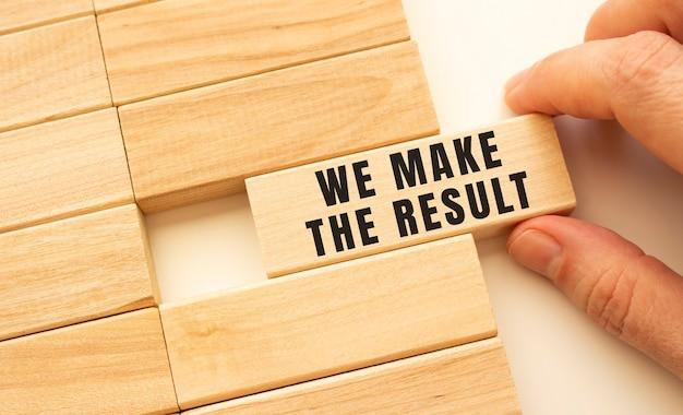 手には、「we maketheresult」というテキストが書かれた木製の立方体があります。