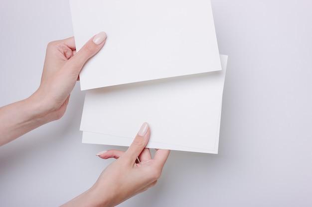 손은 프리젠 테이션 또는 디자인 삽입을 위해 a5 용지를 보유하고 있습니다. 회색 배경에 최소한의 스타일.