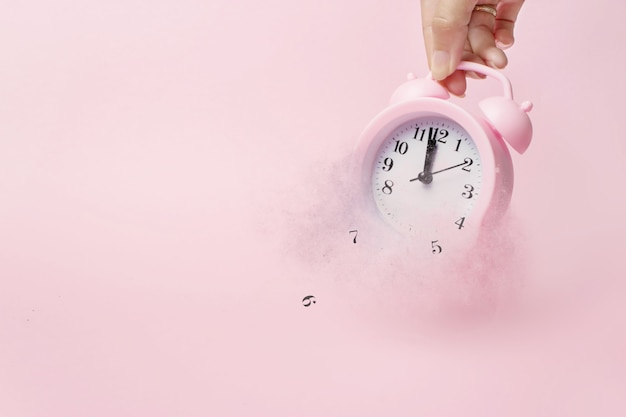 A hand holds alarm clock break down and dispersion to particle. a concept of the time. light pink