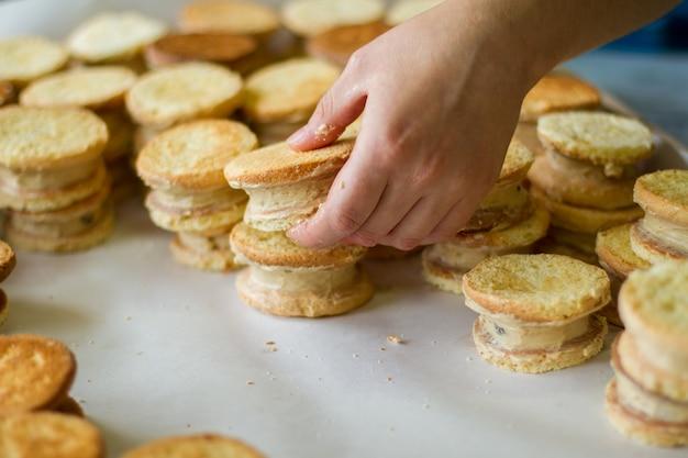 手はクリームでビスケットを保持します。黄色のクッキーサンドイッチ。女性はお菓子を用意します。ペストリーの簡単なレシピ。