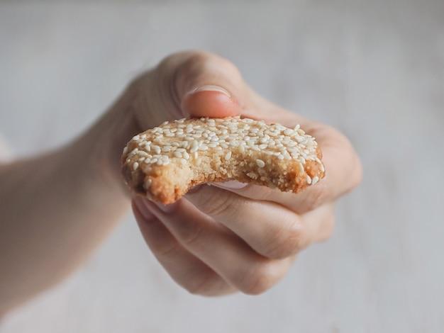 Рука держит укушенные свежие кунжутное печенье
