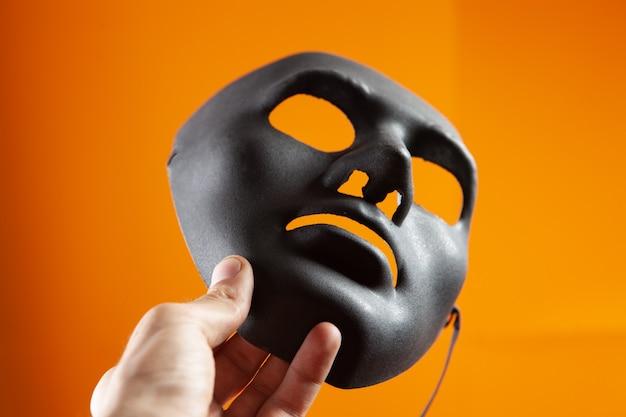 手はオレンジ色の背景に黒の匿名マスクを保持します