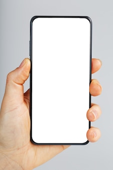 Hand holds black smartphone with blank white screen and modern frameless design isolated on gray surface