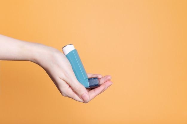 손 오렌지 배경에 천식을 치료하기 위해 파란색 흡입기를 보유