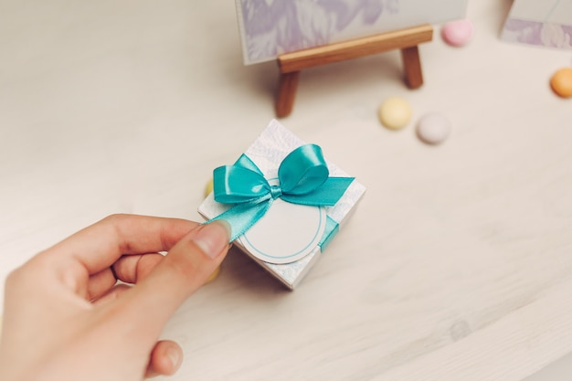 Hand holds bow of blue gift on wooden table