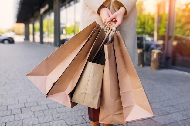 手は茶色の環境に優しいクラフト紙袋を持っています。