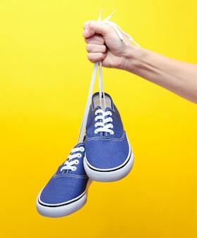 黄色のパステルにレトロなスタイルのヒップスタースニーカーの靴ひもで手を握る