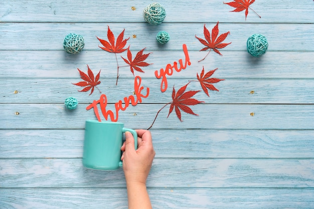 Hand holds ceramic mug with words thank you cut out of paper. seasonal fall flat lay with autumn decorations