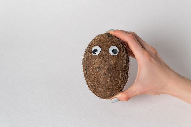 Hand holds the coconut with googly eyes on white background. coconut character with funny face
