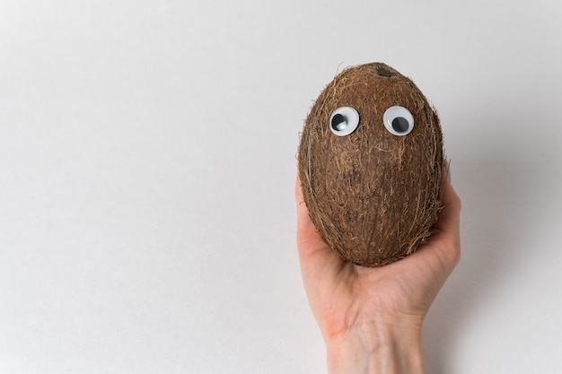 Hand holds coconut with googly eyes on white background. crazy nut. copy space