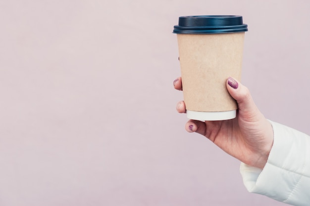 Hand holds coffee in brown cardboard cup with black cap on pink wall
