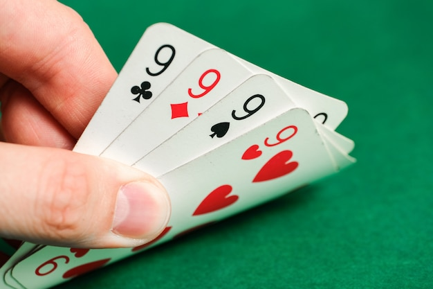 Hand holds a combination in poker - four of a kind on green.