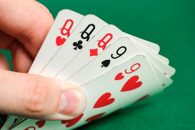 Hand holds a combination in poker - full house on green.