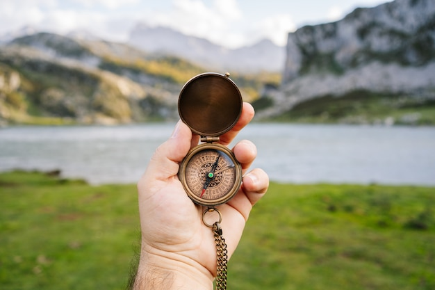 A hand holds a compass in a mountain and lake landscape