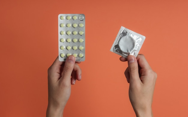 Hand holds condoms in packaging, birth control pills on orange paper