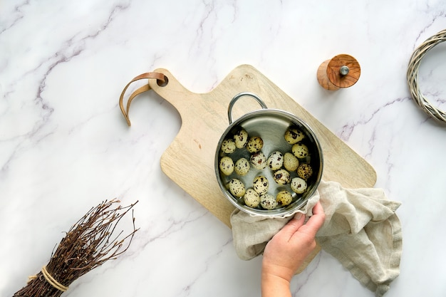 Hand holds cooking pot with quail eggs