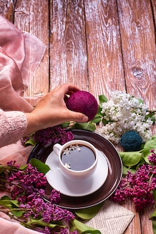 Hand holds a cup of morning coffee with spring lilac flowers branches blossoming on wooden background view from above. flat lay underground style. expensive colors. creative design of flowers.