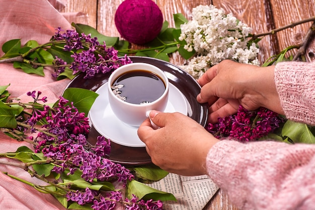 Hand holds a cup of morning coffee with spring lilac flowers branches blossoming on wooden background view from above flat lay underground style