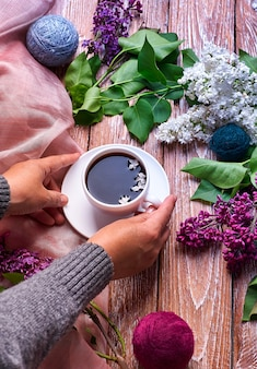Hand holds a cup of morning coffee with spring lilac flowers branches blossoming on wooden background view from above.