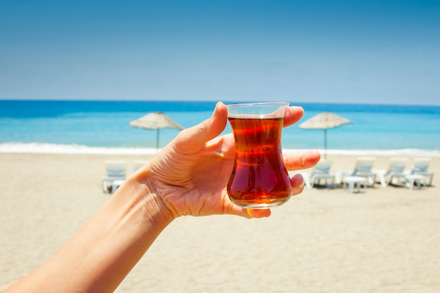 Hand holds a cup with traditional turkish tea.