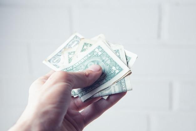 흰색 바탕에 달러 지폐를 들고 있는 손