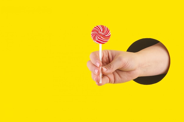 Hand holds edible sweet multi-colored cane-shaped lollipop through a hole