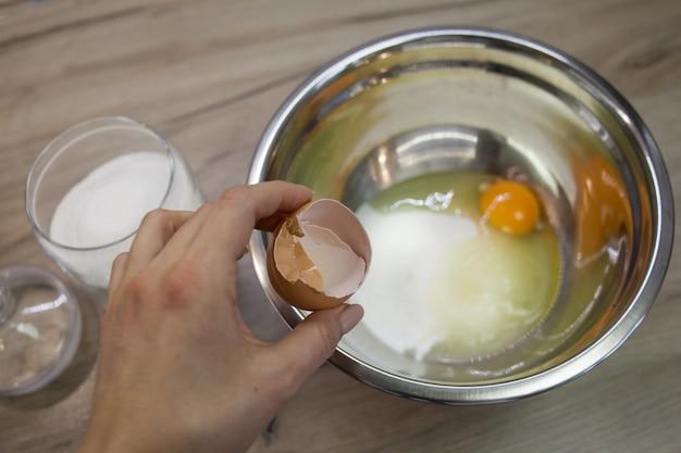 手は砂糖と卵のボウルの背景に卵殻を保持します