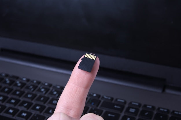 Hand holds flash drive,micro sd memory card adapter on laptop. close up