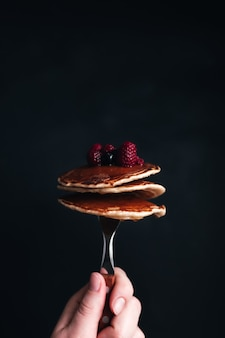Hand holds a fork with juicy pancakes with berries and honey. high quality photo