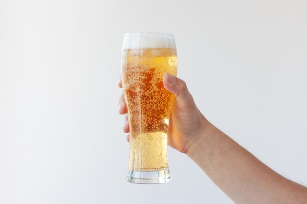 A hand holds a full glass of light beer with bubbles and foam on a white background.