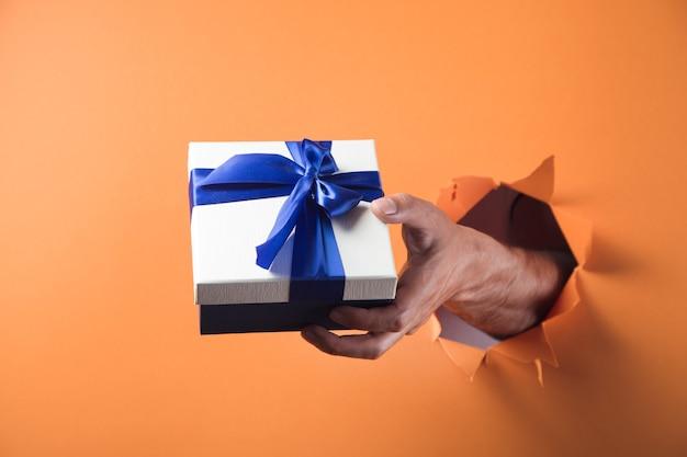 手はオレンジ色の背景にギフトボックスを保持します