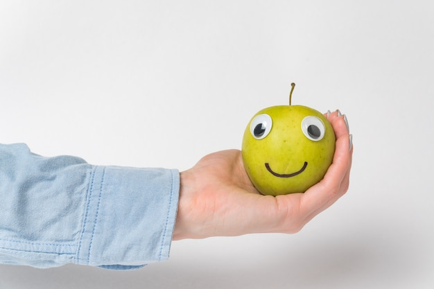 Hand holds green apple-smiley with googly eyes. funny apple on white background