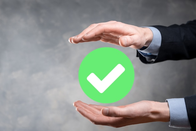 Hand holds green icon check mark,check mark sign, tick icon,right sign,circle green checkmark button,done.on dark background.banner.copy space.place for text.