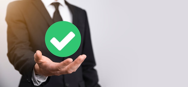Hand holds green icon check mark,check mark sign, tick icon,right sign,circle green checkmark button,done.on grey background.banner.copy space.place for text.