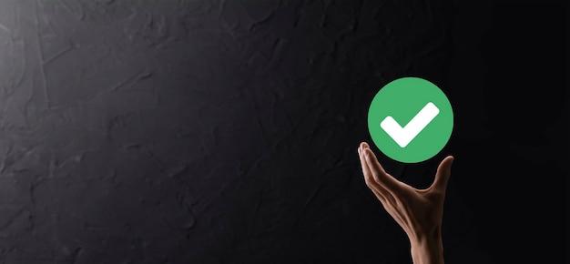 손 보유 녹색 아이콘 확인 표시, 확인 표시 기호, 눈금 아이콘, 오른쪽 기호, 원 녹색 확인 표시 버튼, 완료. 어두운 배경에서. 배너입니다. 공간 복사입니다. 텍스트를 위한 장소입니다.