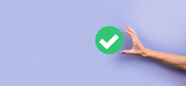 손 보유 녹색 아이콘 확인 표시, 확인 표시 기호, 눈금 아이콘, 오른쪽 기호, 원 녹색 확인 표시 버튼, 완료. 회색 배경에. 배너. 공간 복사. 텍스트를 위한 장소입니다.