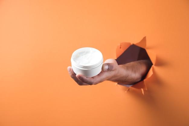 Hand holds hand cream on orange background